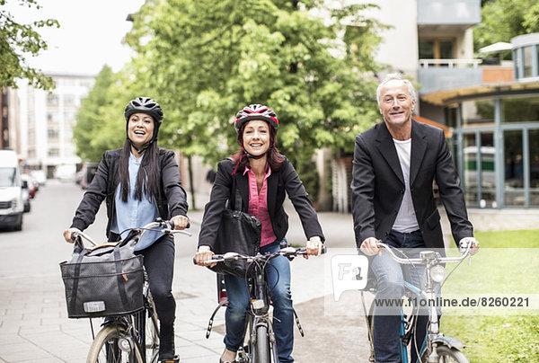 Glückliche Geschäftsleute mit dem Fahrrad auf der Straße