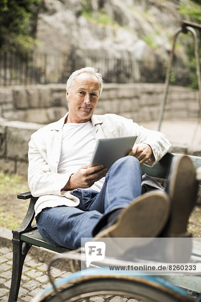 Portrait of businessman with feet up on bicycle holding digital tablet at park