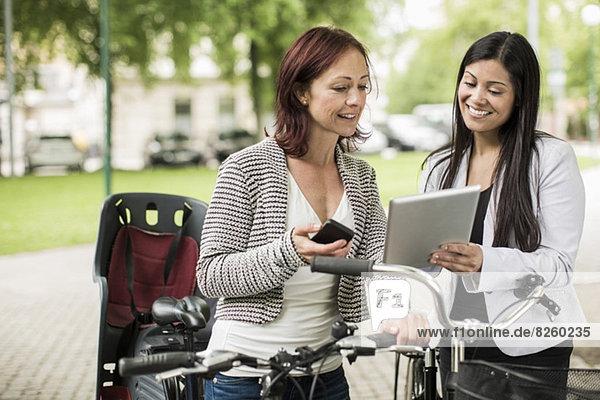 Zufriedene Geschäftsfrauen mit Fahrrädern auf der Straße