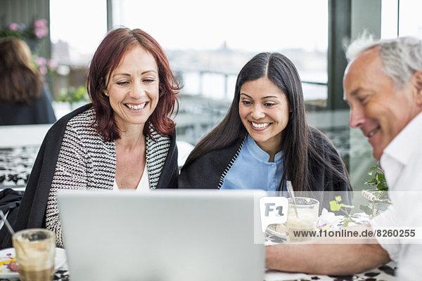 Glückliche Geschäftsleute mit Laptop am Restauranttisch