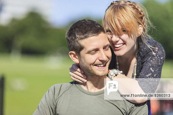 Porträt einer glücklichen Frau  die sich auf den Mann im Park stützt.