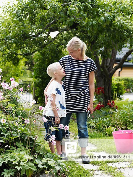 Mother and son standing in garden