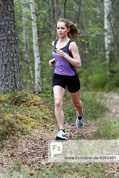 Junge Frau ausgeführt durch Wald