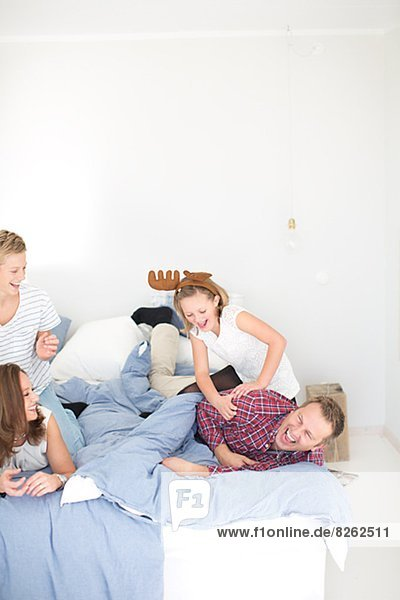 Familie spielen im Bett
