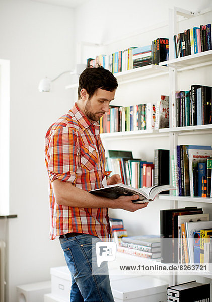 Man reading book by bookshelf