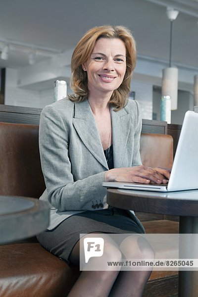Businesswoman sitting in cafe and using laptop