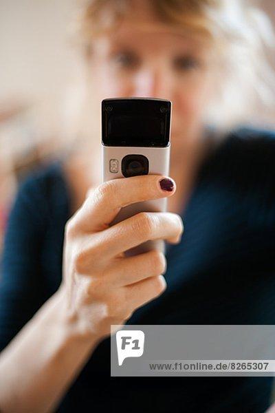 Frau an einer Hauswand telefoniert mit Handy