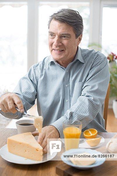 Mann  lächeln  reifer Erwachsene  reife Erwachsene  essen  essend  isst  Frühstück