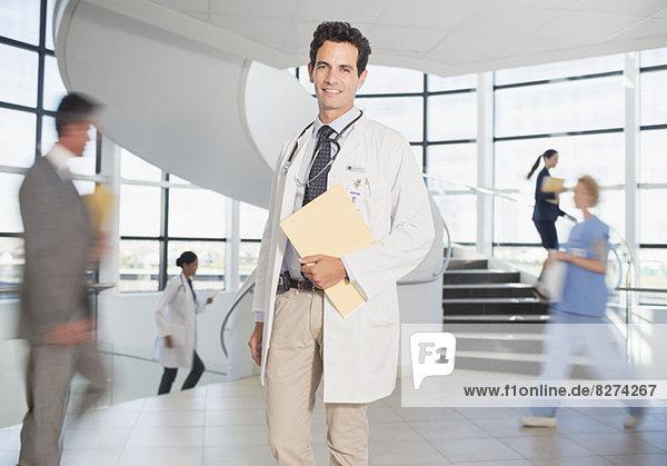 Doctor carrying folders in hospital