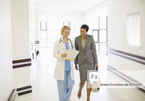Arzt und Geschäftsfrau sprechen im Krankenhausflur