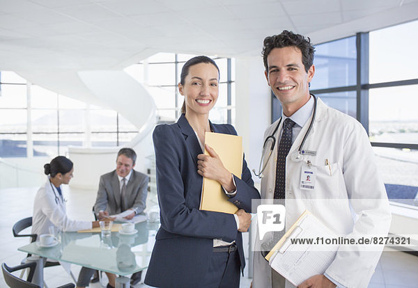 Porträt einer lächelnden Geschäftsfrau und eines Arztes im Meeting