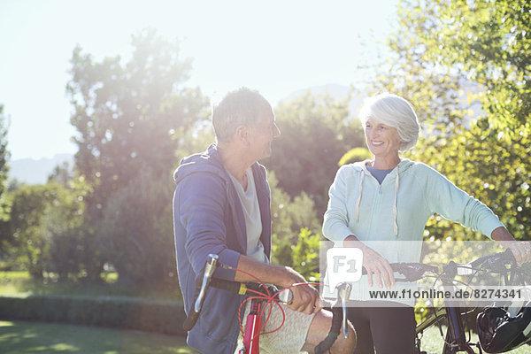 Seniorenpaar mit Fahrrädern im Park