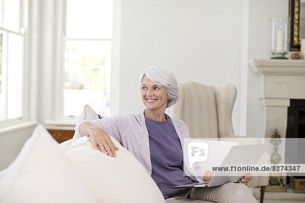 Senior Frau mit Laptop auf dem Sofa