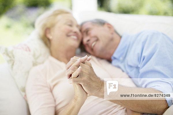 Seniorenpaar hält Hände auf dem Sofa