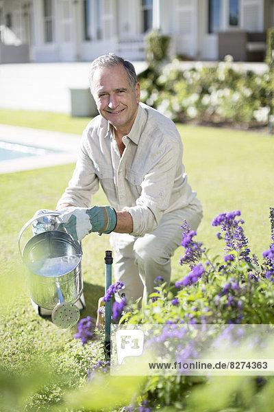 Senior Mann beim Gießen von Pflanzen im Garten