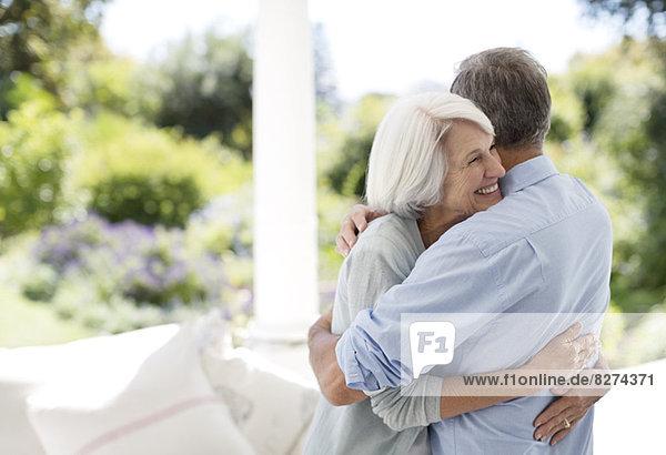 Seniorenpaar umarmt sich auf der Terrasse