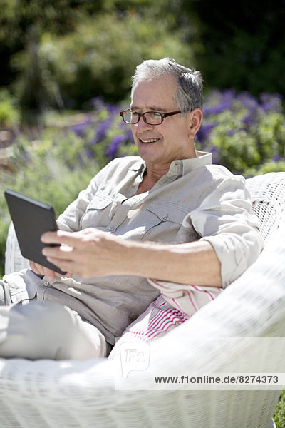 Senior Mann mit digitalem Tablett im Sessel
