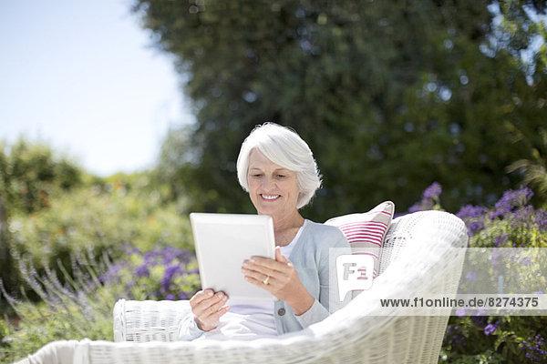 Seniorin mit digitalem Tablett im Sessel