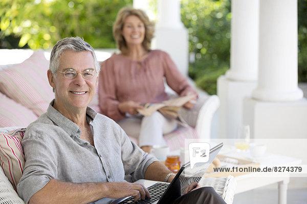 Senior Mann mit Laptop auf der Terrasse