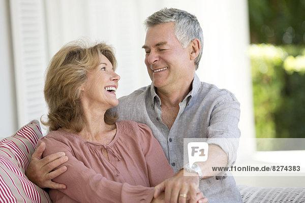 Seniorenpaar im Sessel auf der Terrasse umarmend