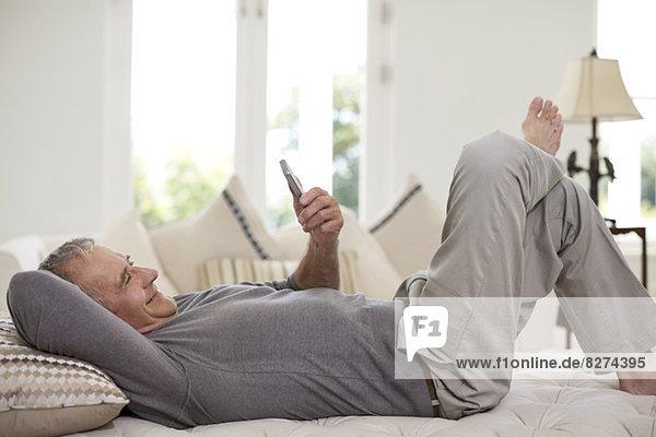 Senior Mann mit Handy im Bett