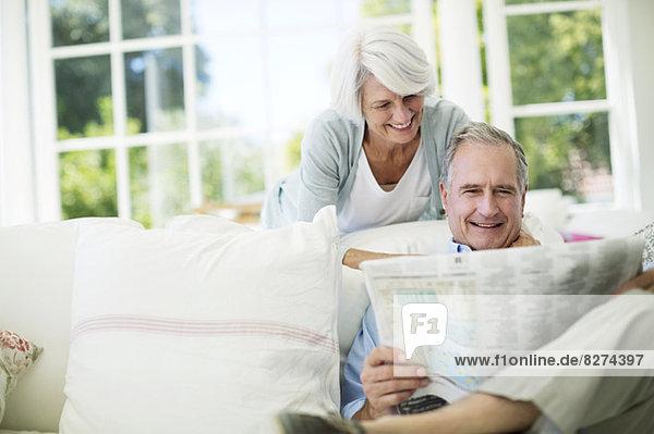 Seniorenpaar liest Zeitung auf dem Sofa