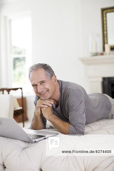 Senior Mann mit Laptop im Wohnzimmer