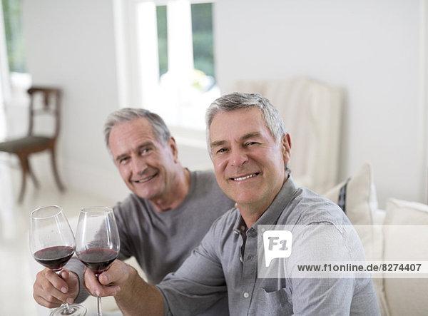 Porträt der Senioren beim Toasten von Weingläsern