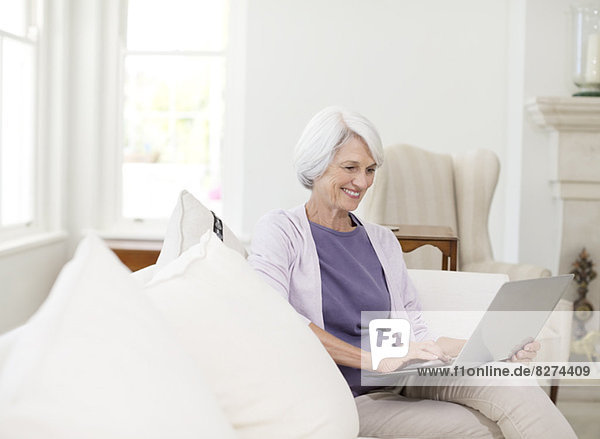 Seniorin mit Laptop auf Sofa im Wohnzimmer
