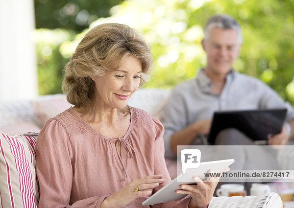 Seniorin mit digitalem Tablett auf der Terrasse