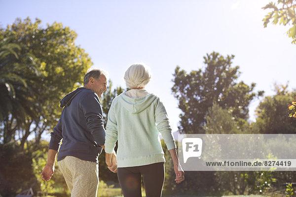 Seniorenpaar hält sich an den Händen und geht im Park spazieren.