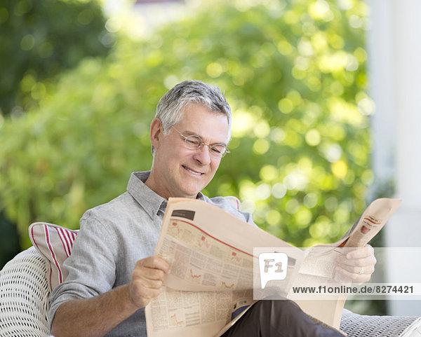 Senior Mann liest Zeitung auf der Terrasse