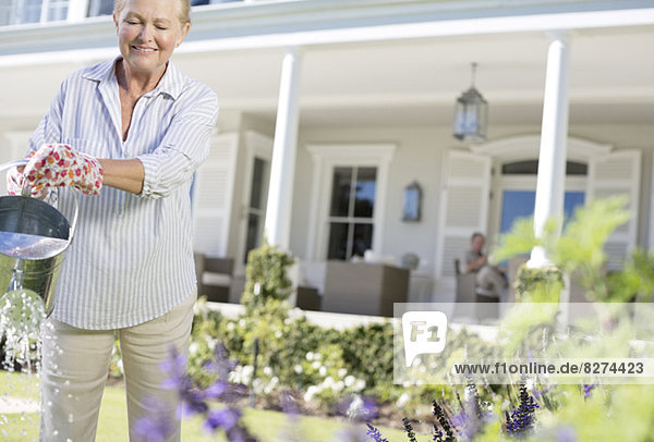 Seniorin beim Gießen von Pflanzen im Garten