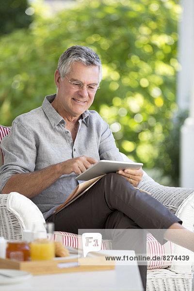 Senior Mann mit digitalem Tablett auf der Terrasse