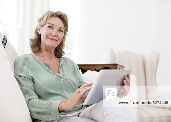 Porträt einer älteren Frau mit digitalem Tablett auf dem Sofa