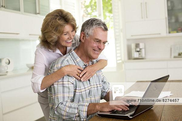 Senior Paar mit Laptop in der Küche
