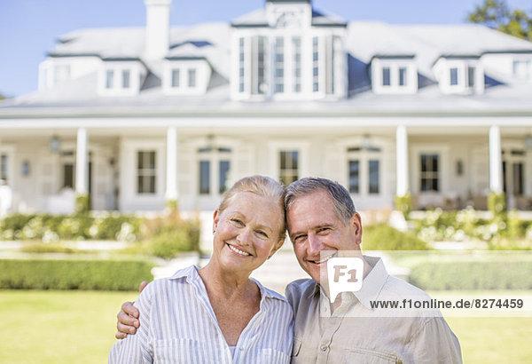 Porträt eines lächelnden Seniorenpaares vor dem Haus