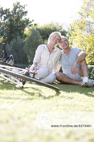 Seniorenpaar sitzend im Park mit Fahrrädern