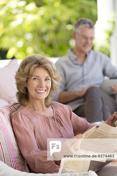 Porträt einer älteren Frau beim Zeitungslesen auf der Terrasse