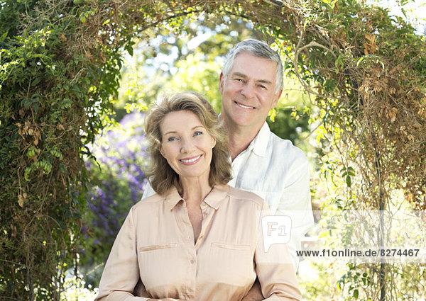 Porträt eines lächelnden Seniorenpaares im Garten