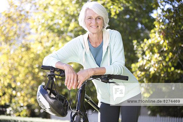 Porträt einer älteren Frau  die sich auf das Fahrrad stützt.