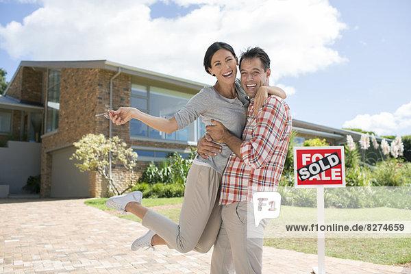Porträt eines begeisterten Paares  das sich vor dem Haus umarmt  mit dem For Sale Schild