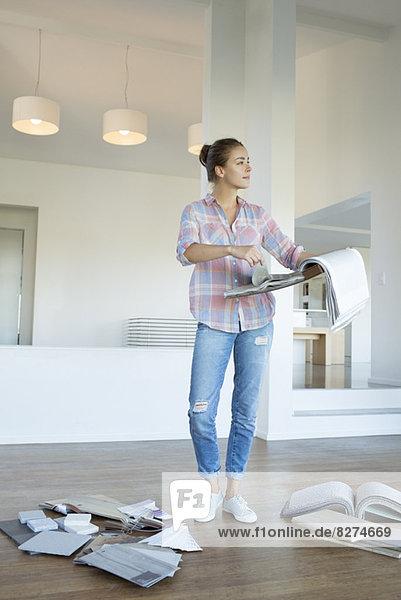 Frau betrachtet Stoffmuster im neuen Haus