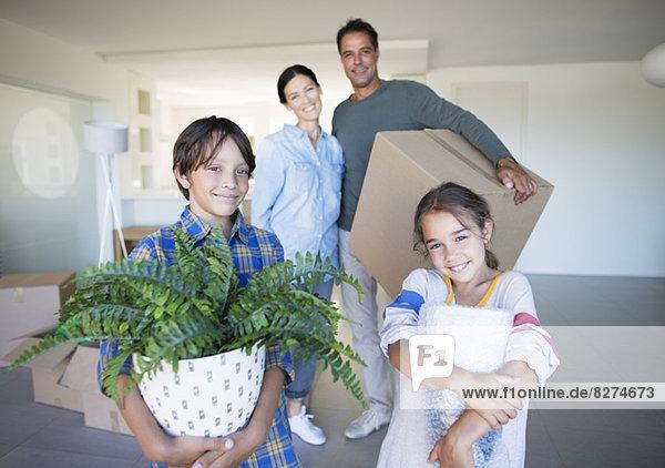 Porträt eines lächelnden Familienbesitzes im neuen Haus