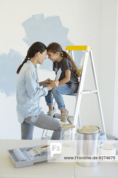 Mutter und Tochter malen Wand blau