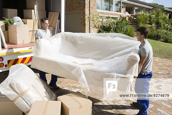 Umzugswagen mit Sofa aus dem Umzugswagen in der Einfahrt