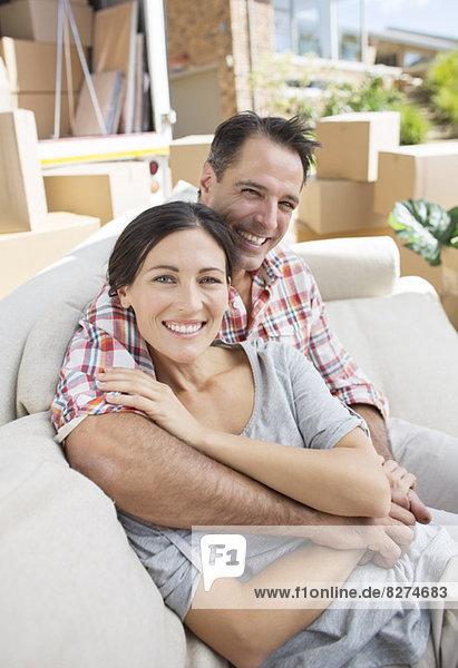 Porträt eines lächelnden Paares  das sich auf dem Sofa in der Einfahrt in der Nähe des Umzugswagens umarmt.