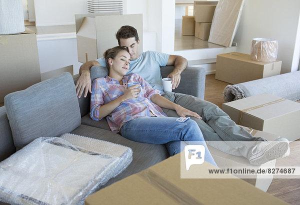 Paar entspannt auf Sofa im neuen Haus