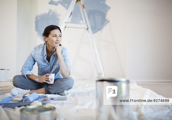 Frau entspannt sich beim Kaffee unter den Malutensilien