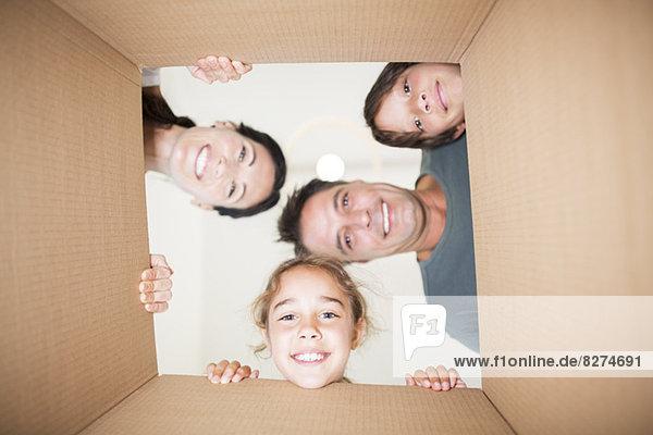 Familie schaut durch den Karton auf die Kamera herab